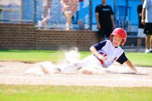 Young baseball player sliding