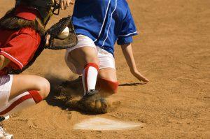 Softball player sliding into home plate