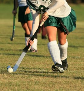 Girls playing field hockey