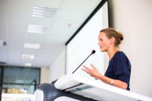 Speaking at podium to audience
