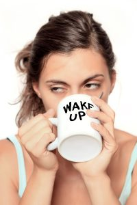 Woman drinking coffee due to lack of sleep