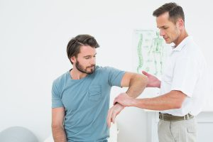 Physical therapist helps man with shoulder impingement