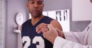 An athlete getting checked by a doctor for a boxer's fracture