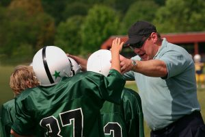 Football coach teaching young players