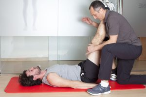 Physical therapist stretching a patient after an adductor strain
