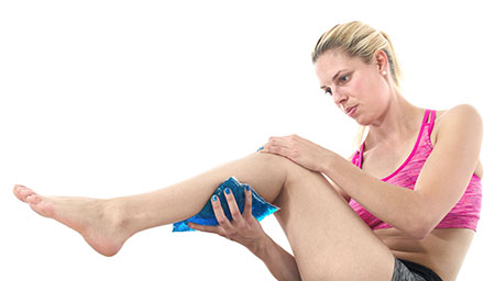 Woman applying a cold pack to her calf injury