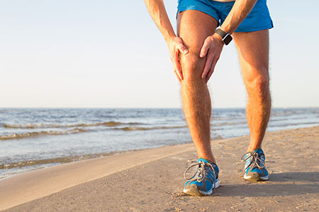 Man with pain running after a knee injury