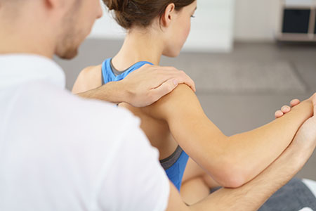 Physical therapist rehabbing a woman after shoulder surgery