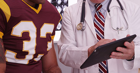 NFL player reviewing his injury with a doctor